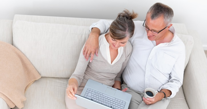 Modern mature couple using laptop on couch
